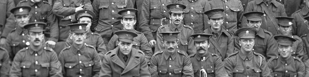 Group portrait of fifty or so Soldiers taken by photographer D C Harries around 1916.